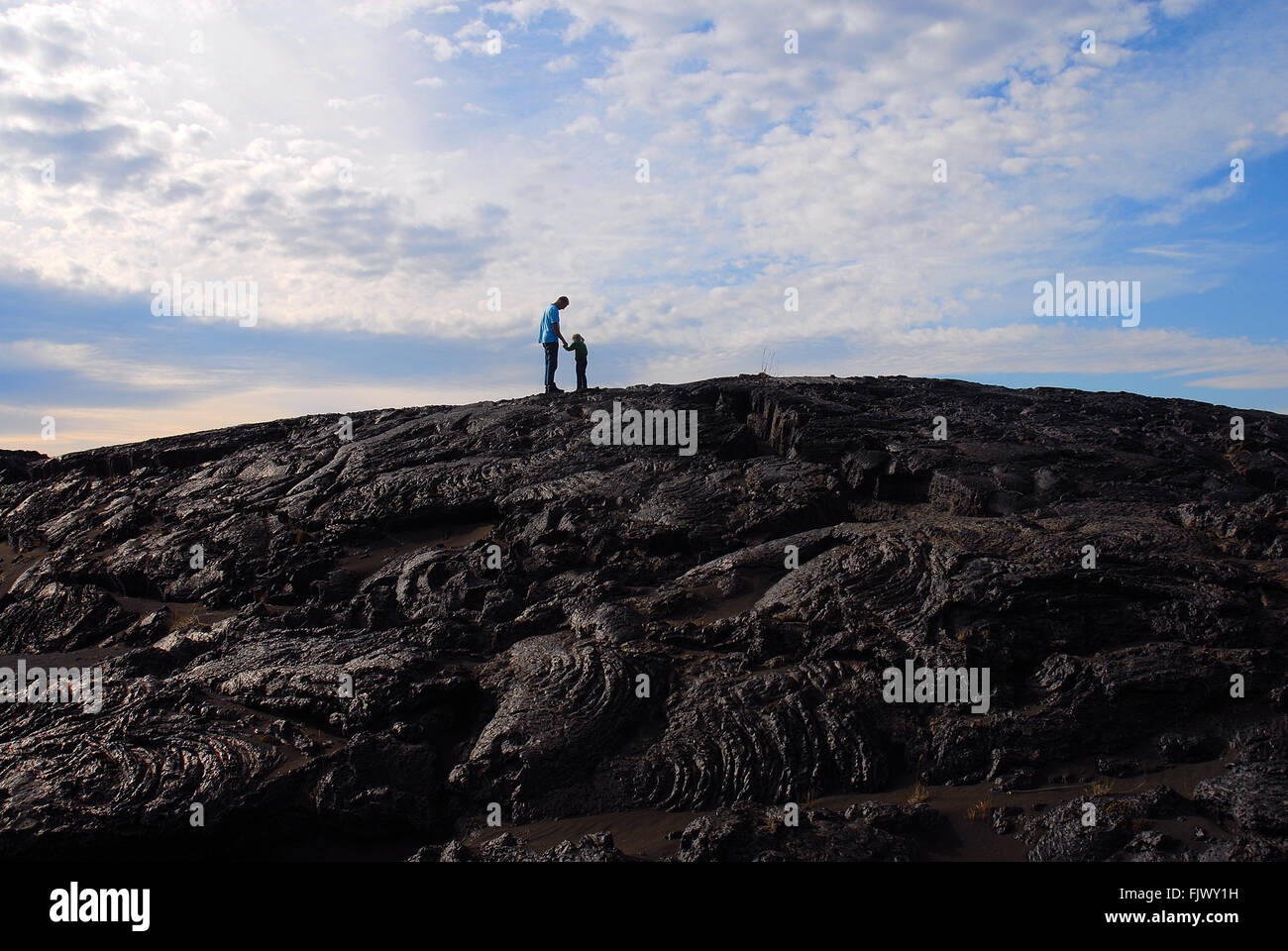 Low Angle View Of Child And Father Standing On Mountain Against Cloudy Sky - Stock Image