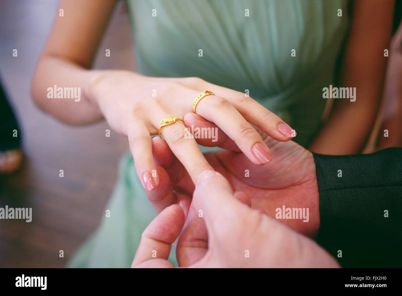 Cropped Image Of Groom Putting Wedding Ring On Bride Finger - Stock Image