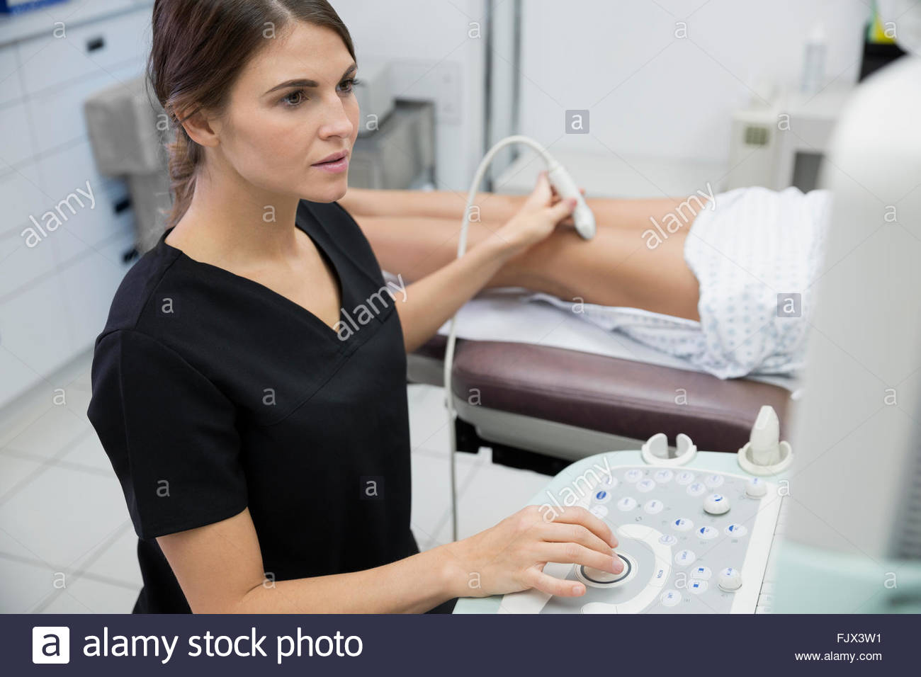 Technician treating varicose veins with ultrasound equipment - Stock Image