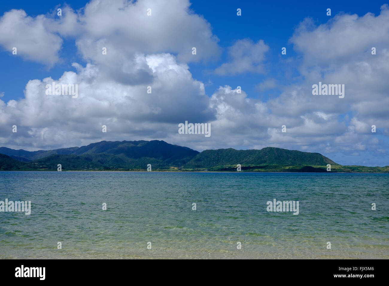 Scenic View Of Sea And Mountains Against Cloudy Sky - Stock Image