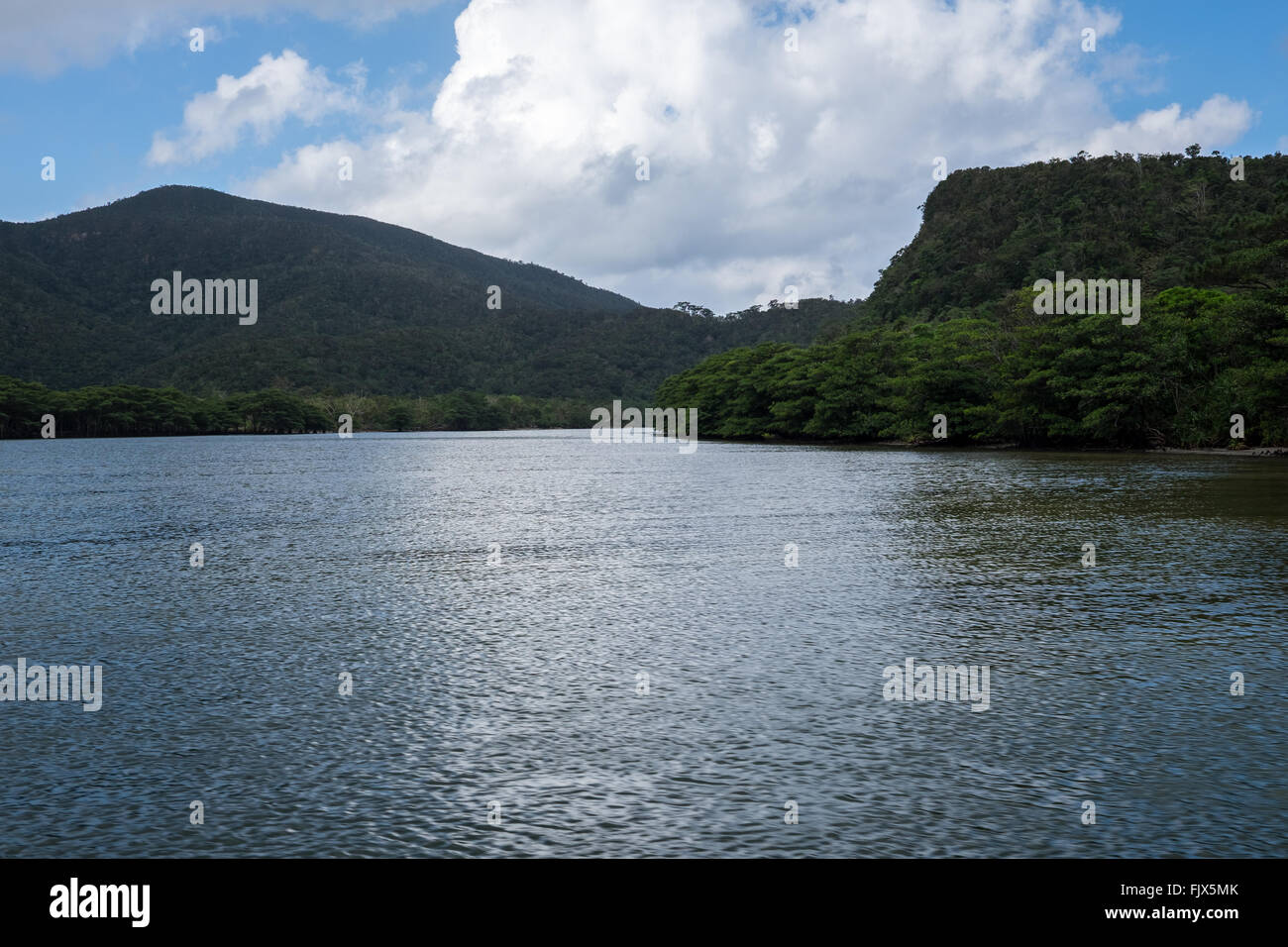 Scenic View Of Mountains By Lake Against Cloudy Sky - Stock Image