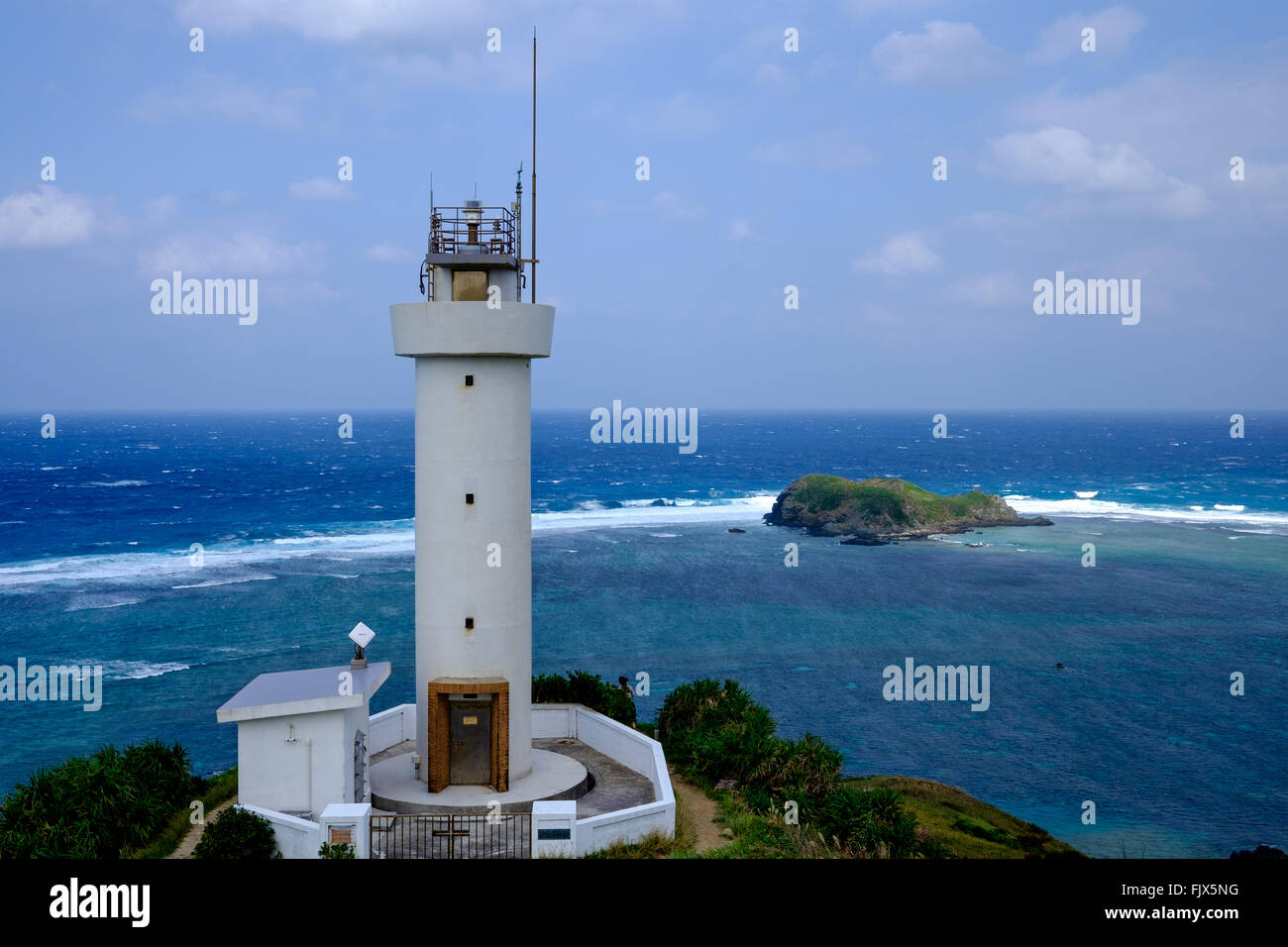 Lighthouse On Sea Against Cloudy Sky - Stock Image