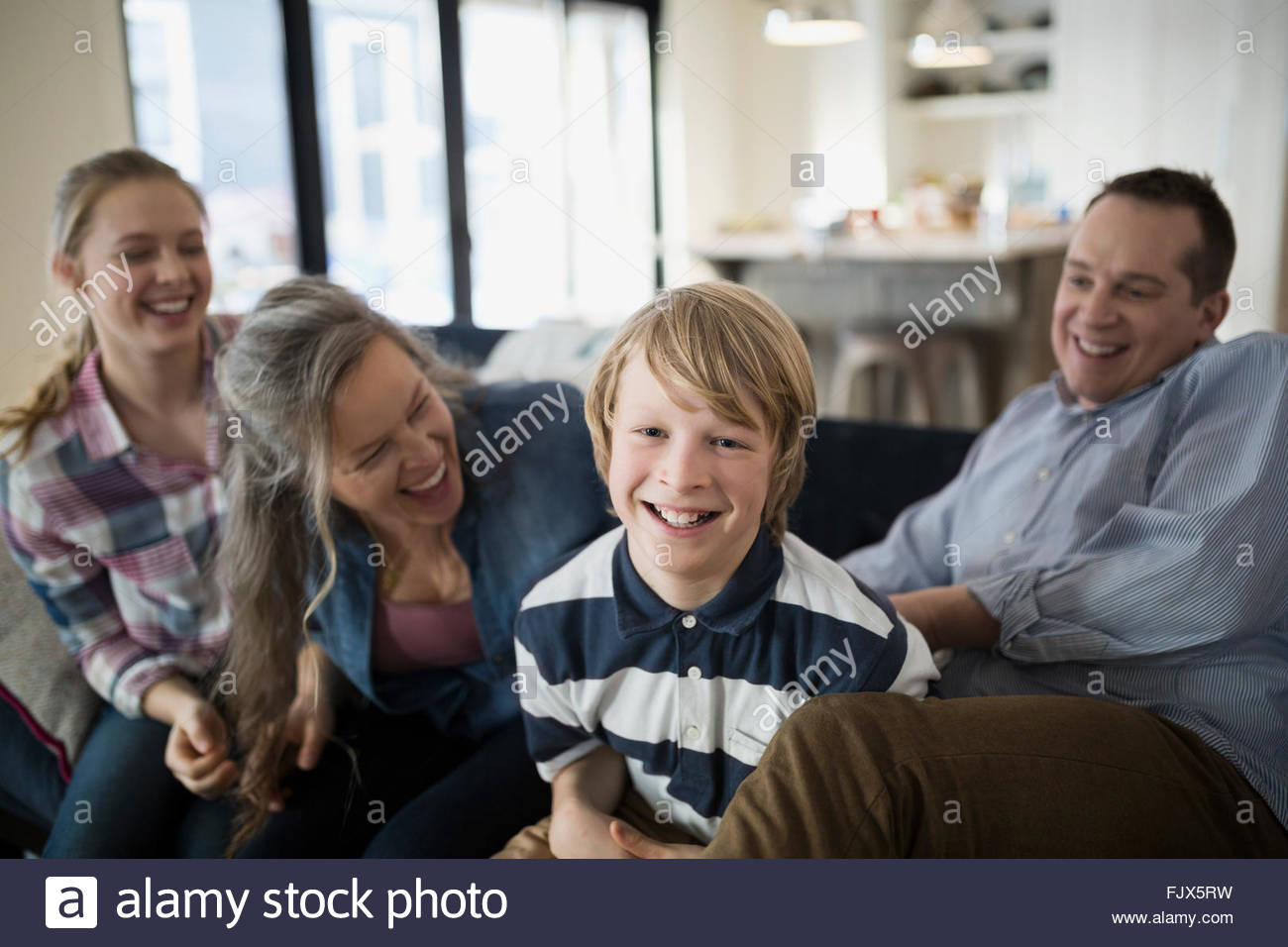 Portrait smiling boy with family living room sofa - Stock Image