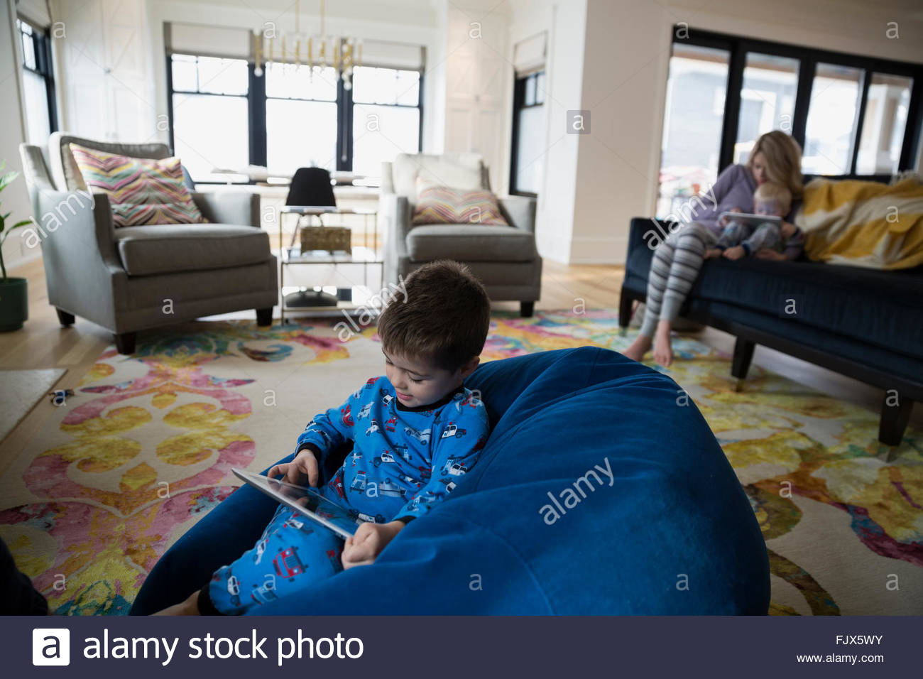 Boy pajamas using digital tablet bean bag chair - Stock Image