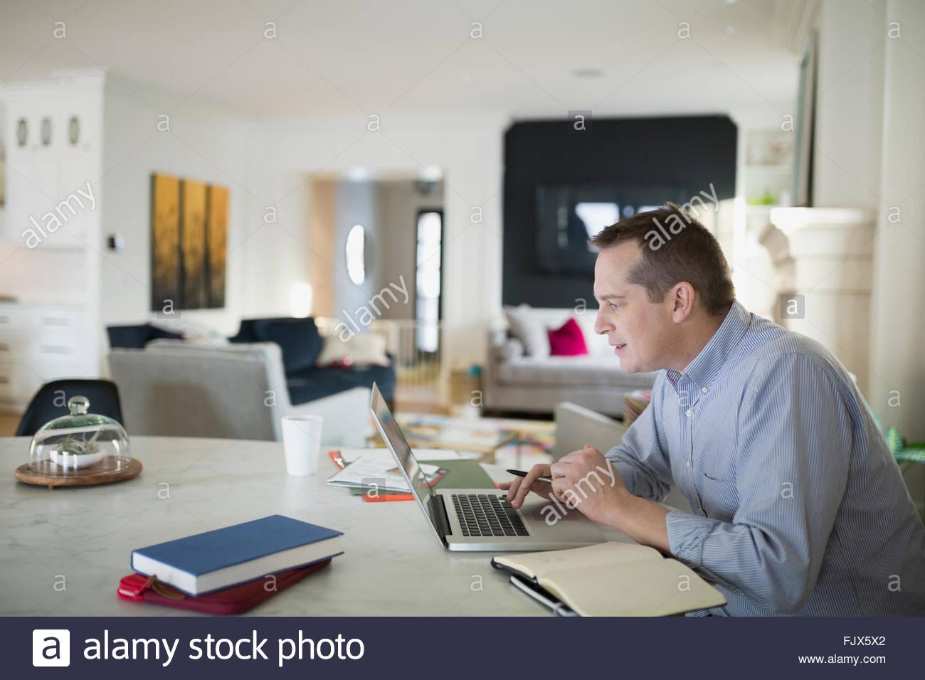 Man working at laptop at kitchen table - Stock Image