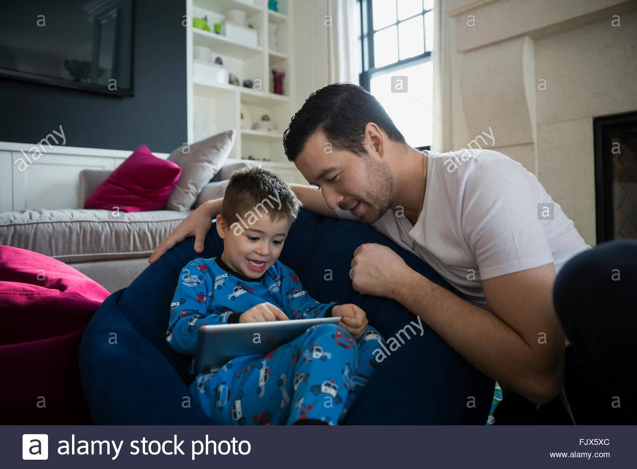 Father and son in pajamas using digital tablet - Stock Image