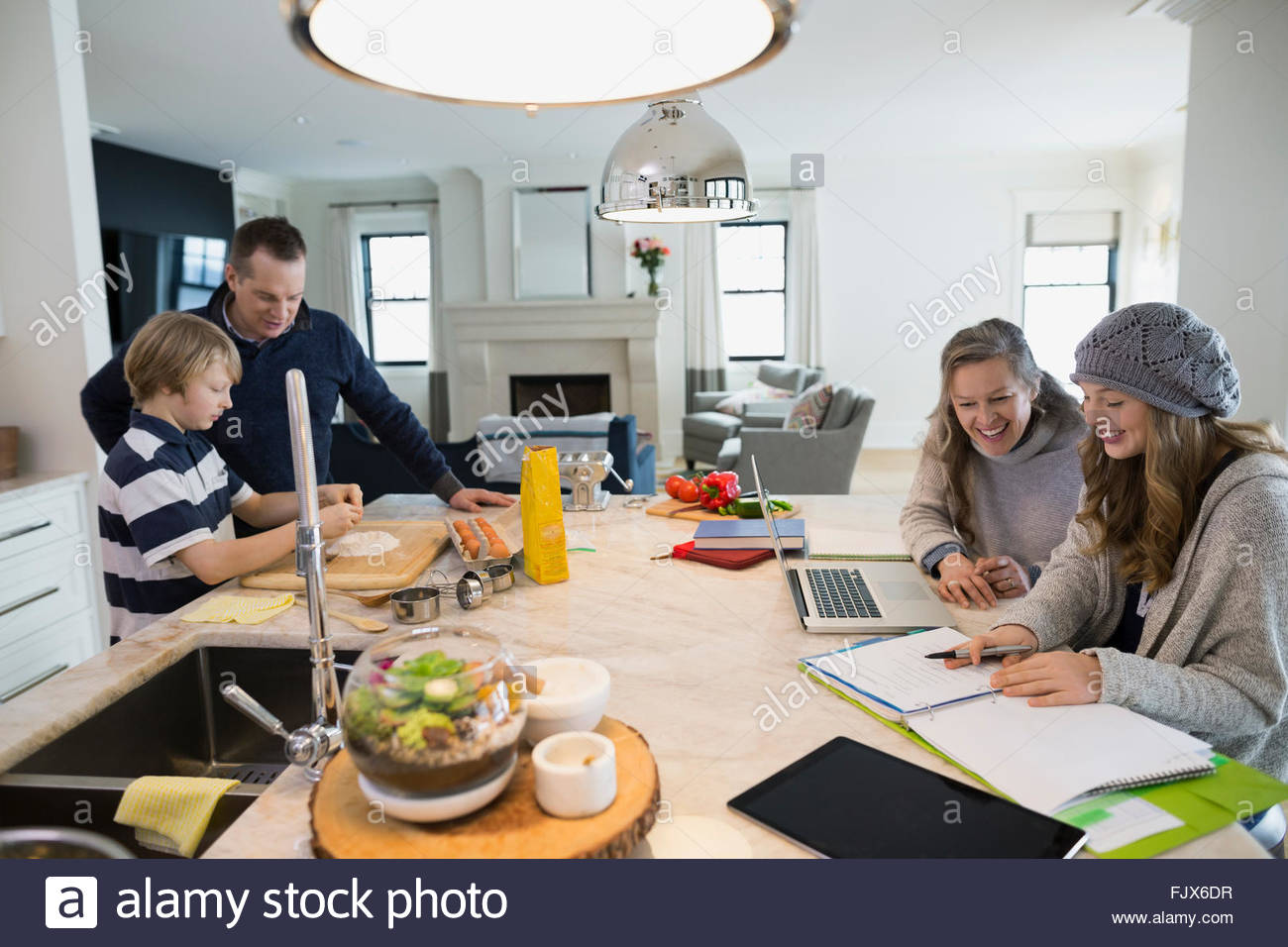 Family baking and doing homework at kitchen island - Stock Image