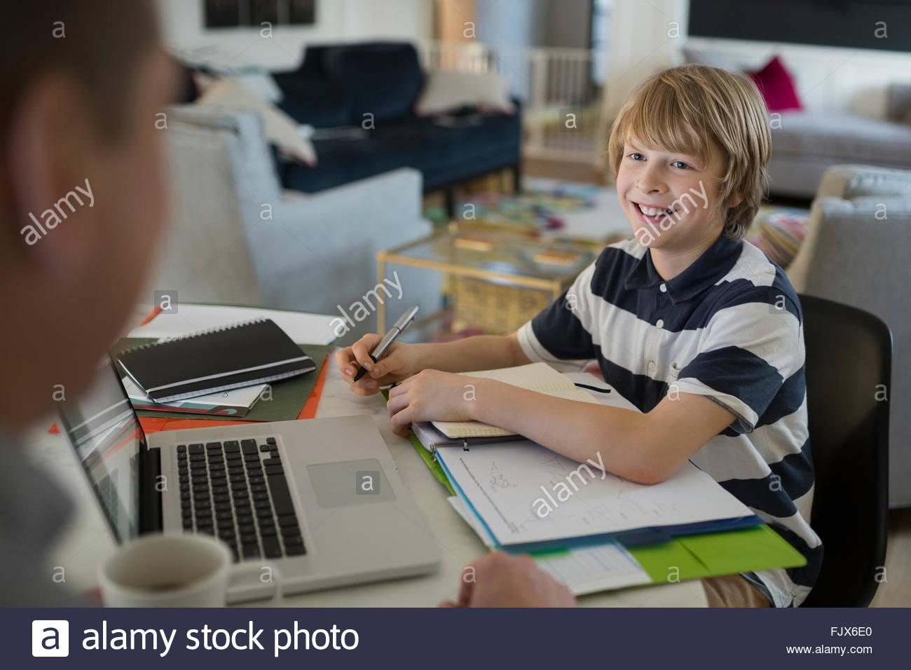 Son doing homework smiling at father - Stock Image