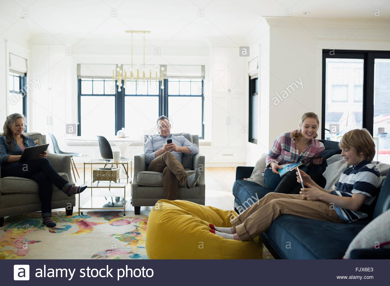 Family relaxing using technology in living room - Stock Image