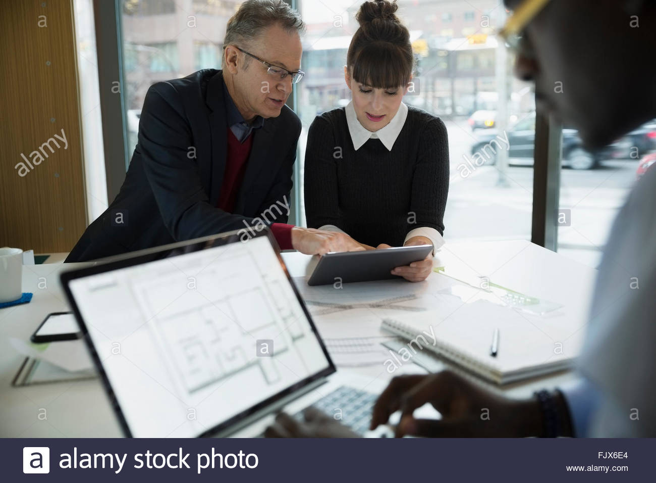Architects using technology in urban office - Stock Image