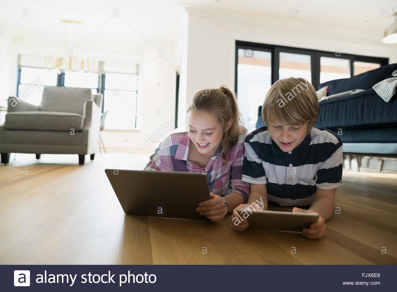 Brother sister using digital tablets living room floor - Stock Image
