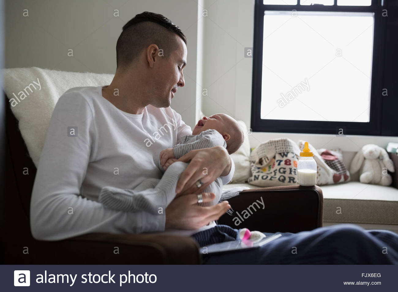 Father holding baby son in nursery - Stock Image