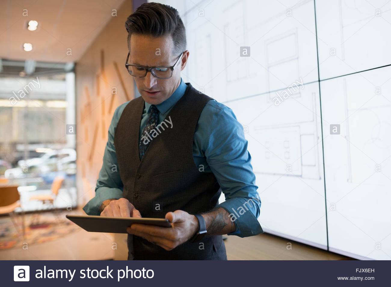 Architect using digital tablet at projection screen - Stock Image