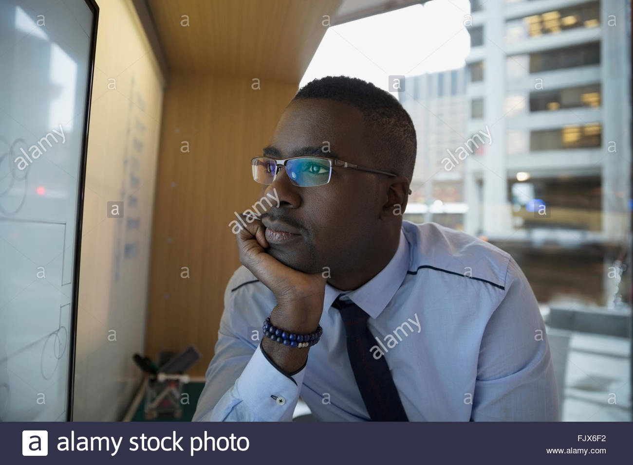 Pensive architect viewing digital blueprint on computer monitor - Stock Image