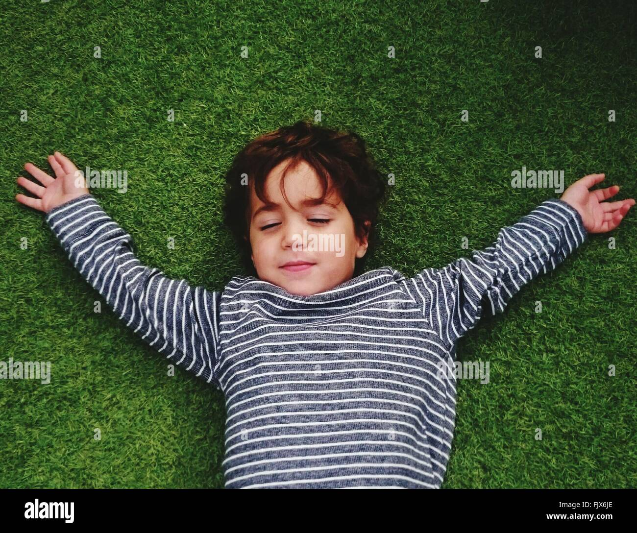 High Angle View Of Cute Boy Resting On Grassy Field - Stock Image