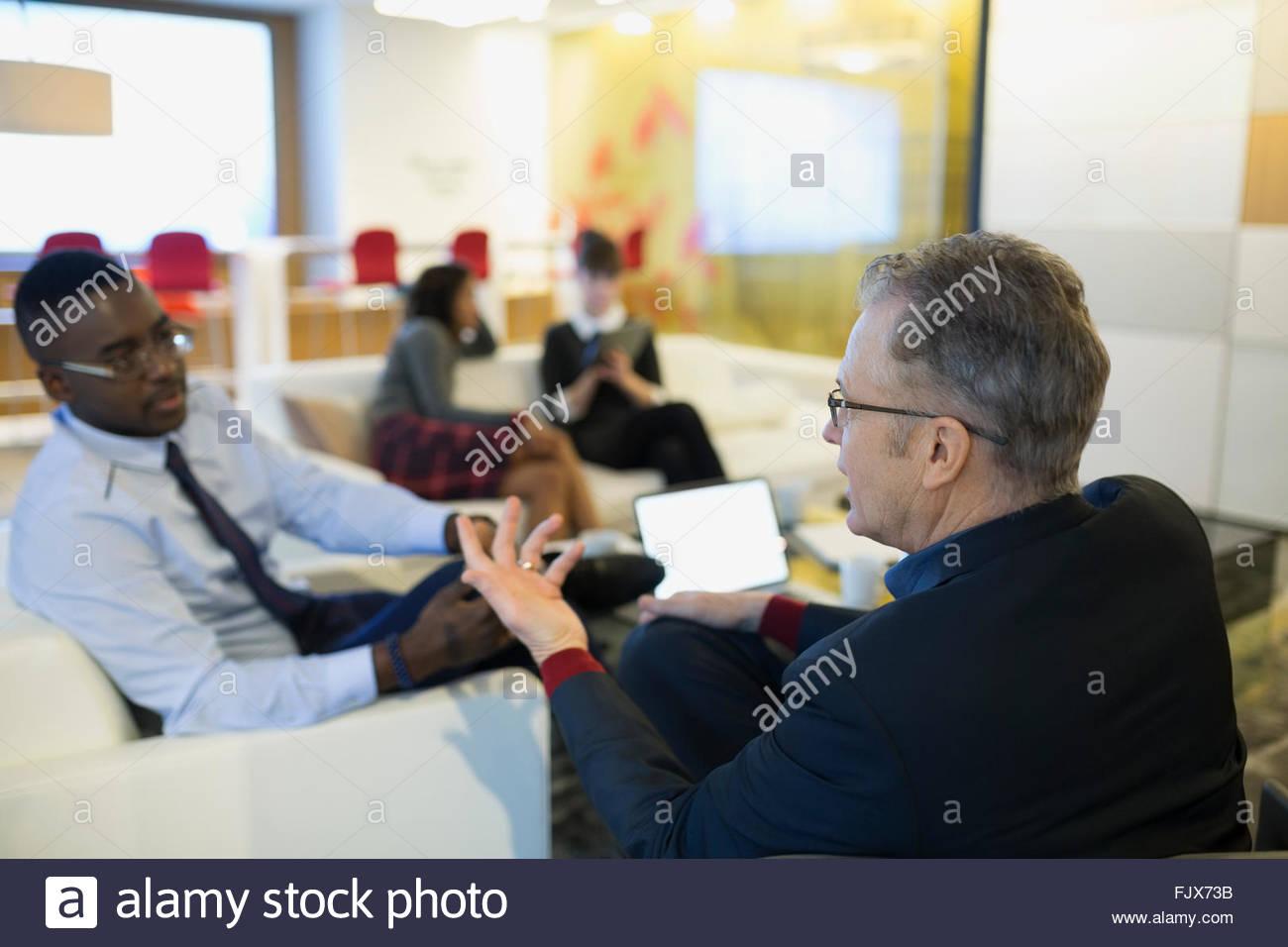 Businessmen talking in office lobby - Stock Image