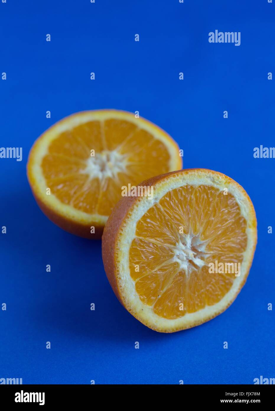 A sliced orange against a blue background. - Stock Image