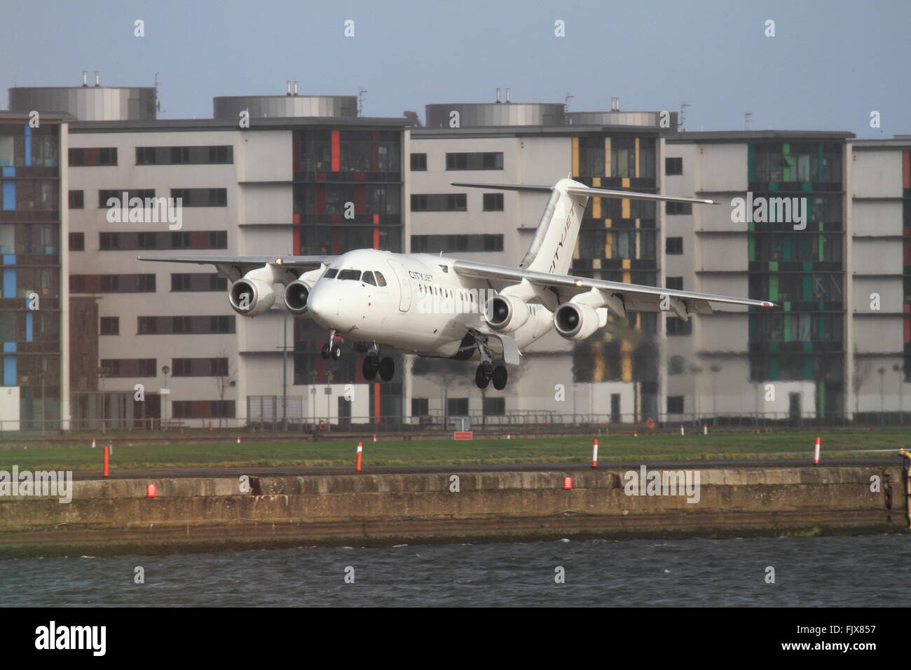 Bae 146 (EI-RJO)— CityJet lands at London City Airport, with the UEL Campus backdrop. Stock Photo