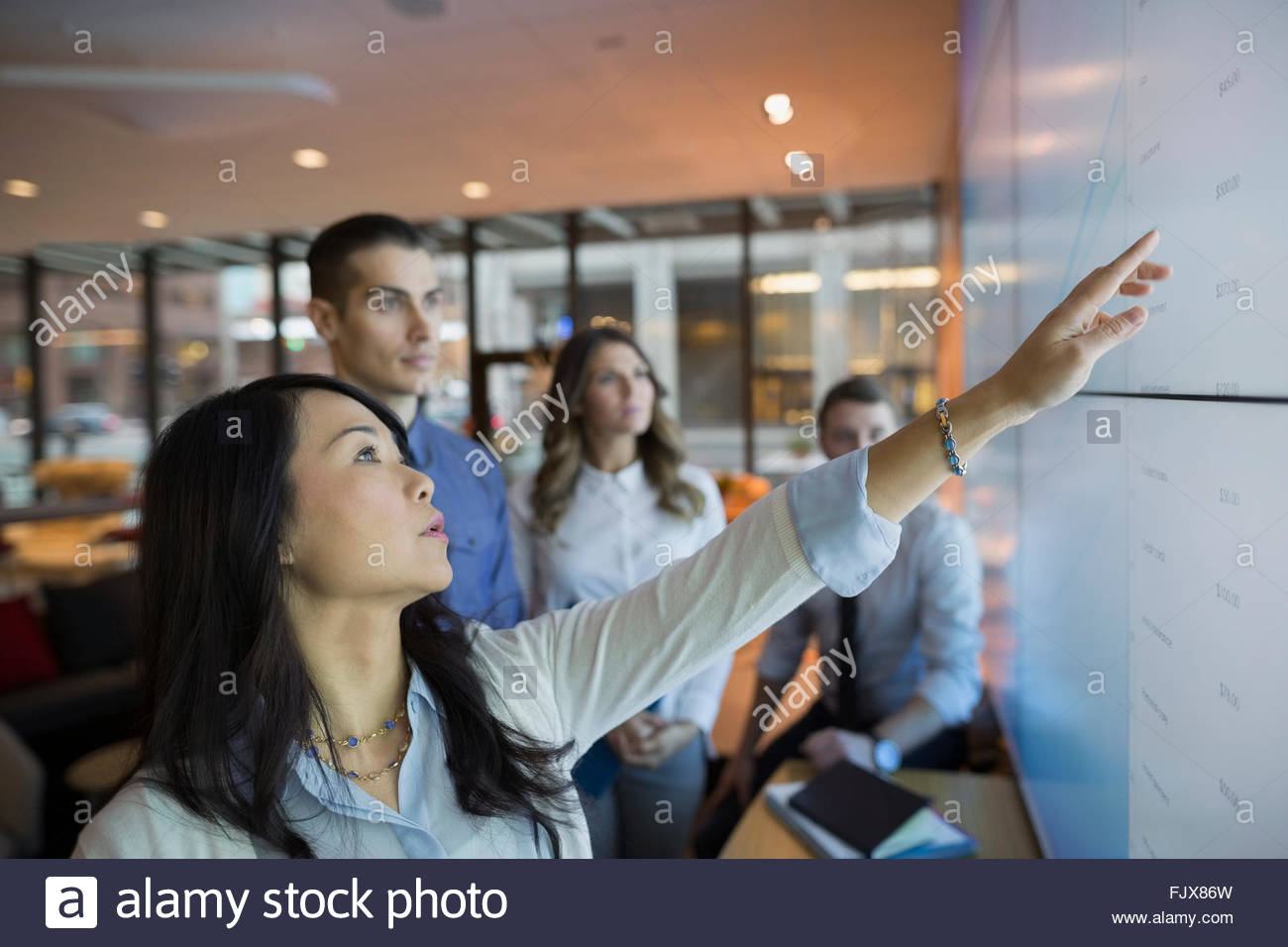 Business people pointing at projection screen conference room - Stock Image