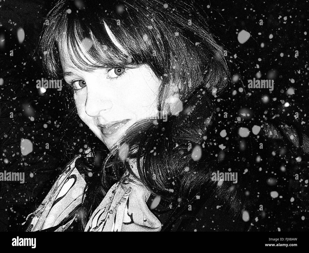 Portrait Of Beautiful Woman During Snow Fall At Night - Stock Image
