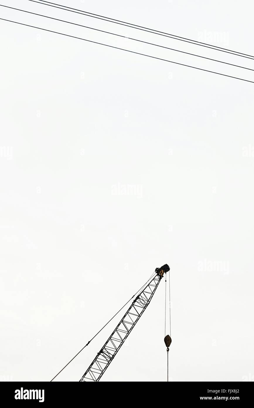 Low Angle View Of Crane And Electricity Cables Against Clear Sky - Stock Image