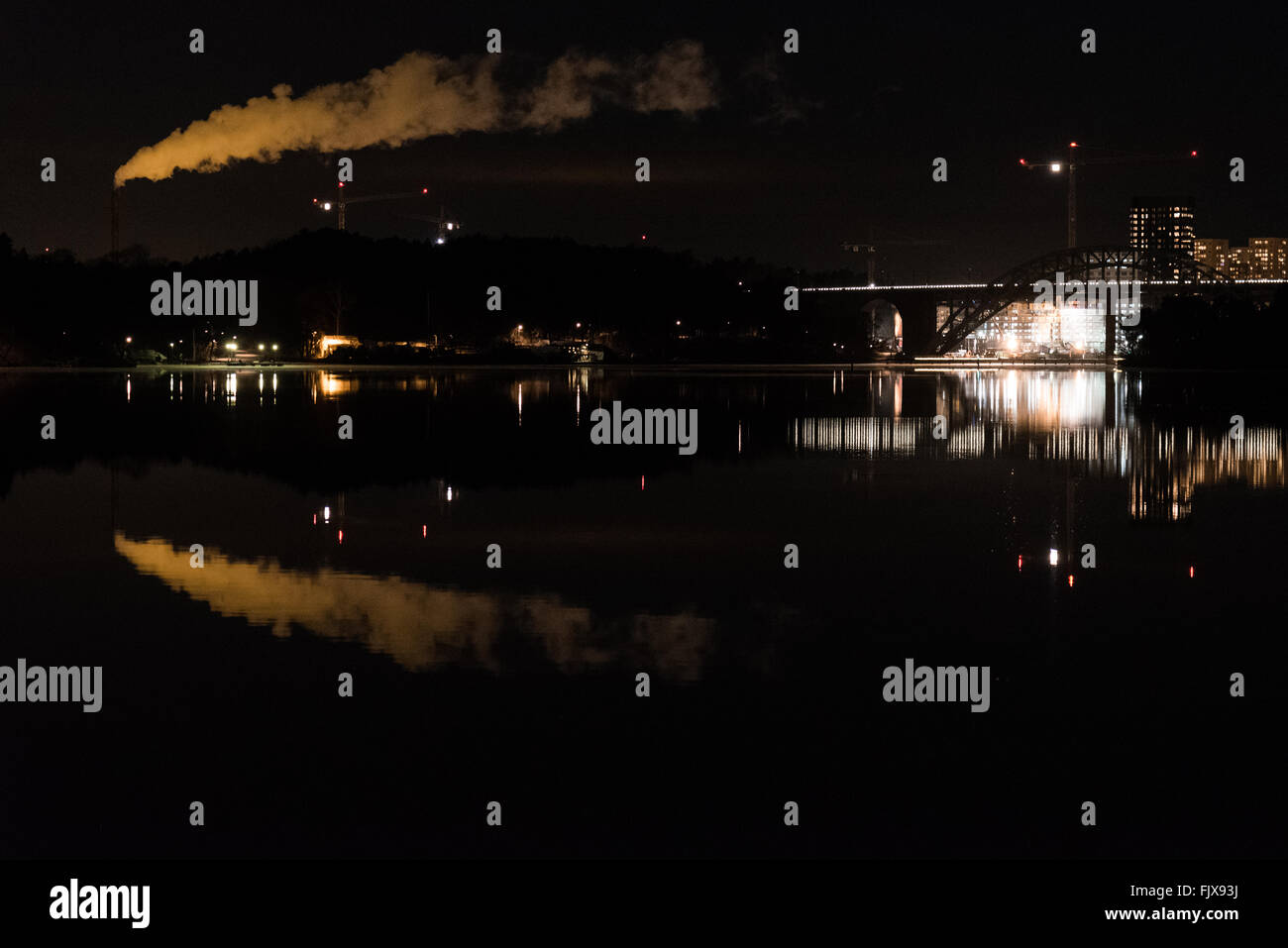 Smoke Stack Emitting Pollution With Reflection In River Against Sky - Stock Image