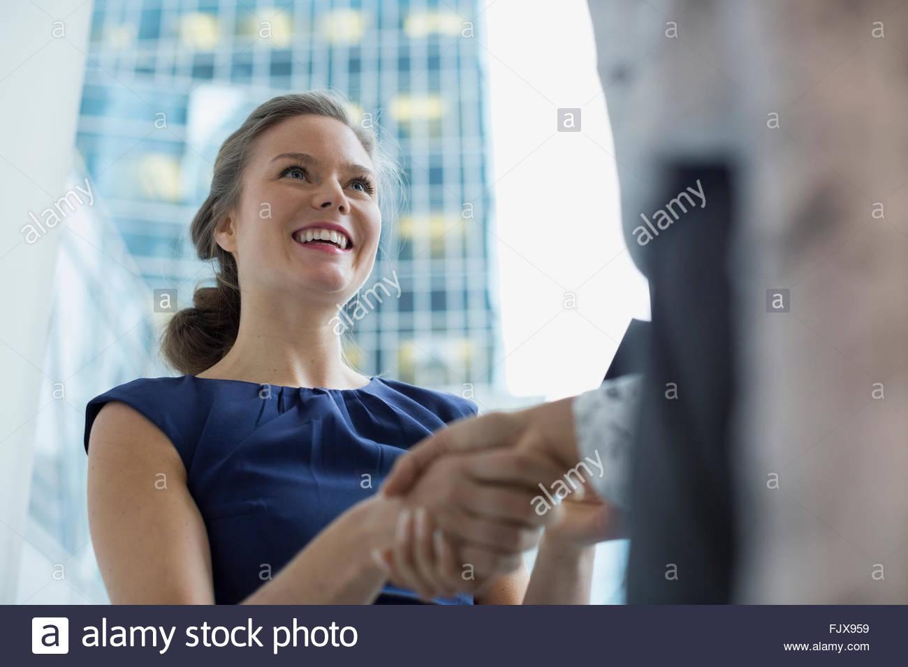 Smiling young businesswomen handshaking - Stock Image