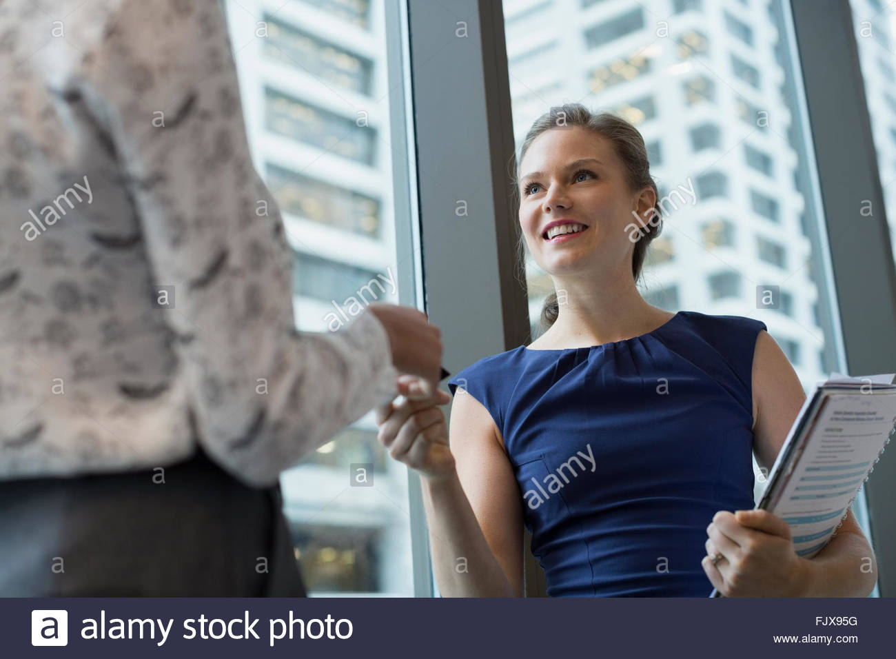 Smiling young businesswoman giving business card to colleague - Stock Image
