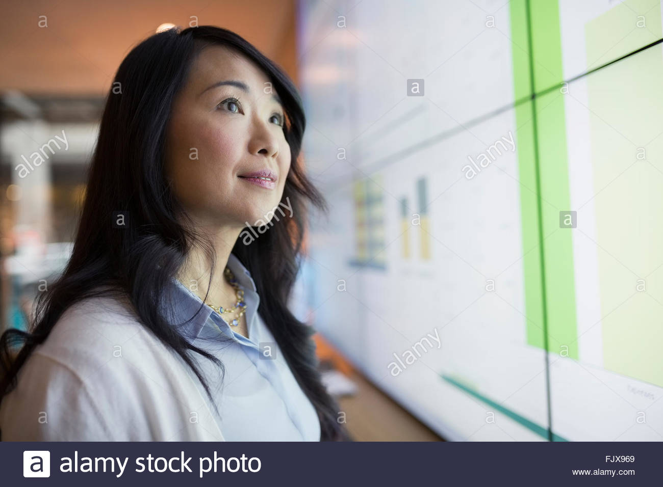Curious businesswoman looking up at projection screen - Stock Image