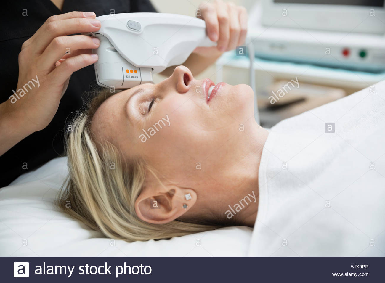 Aesthetic technician using ultrasound equipment on womans face - Stock Image