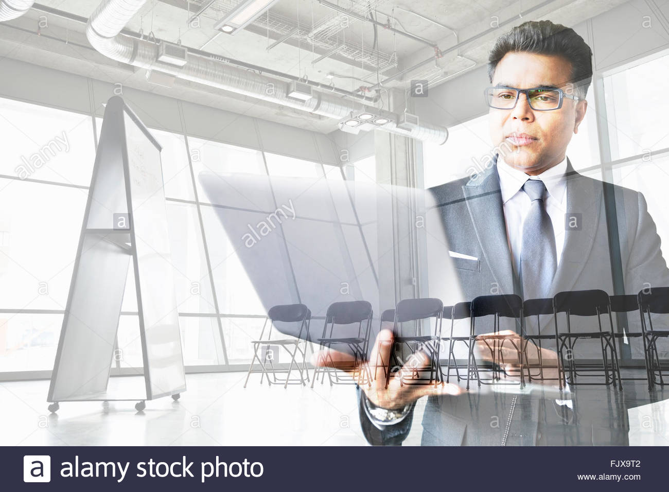 Digital composite businessman working at laptop conference room - Stock Image