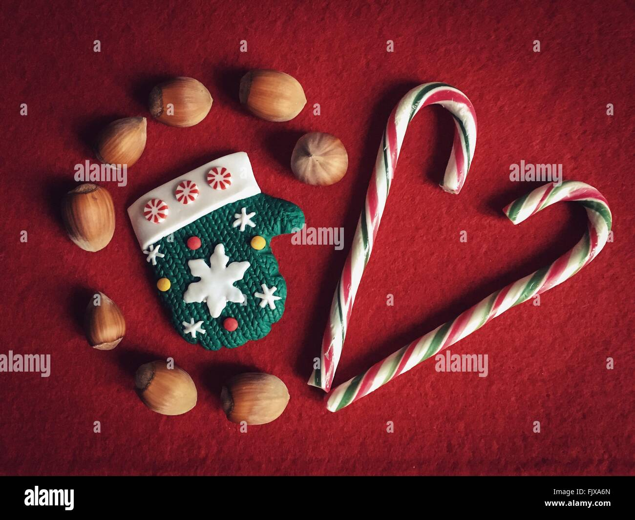High Angle View Of Candies And Hazelnuts On Red Table - Stock Image