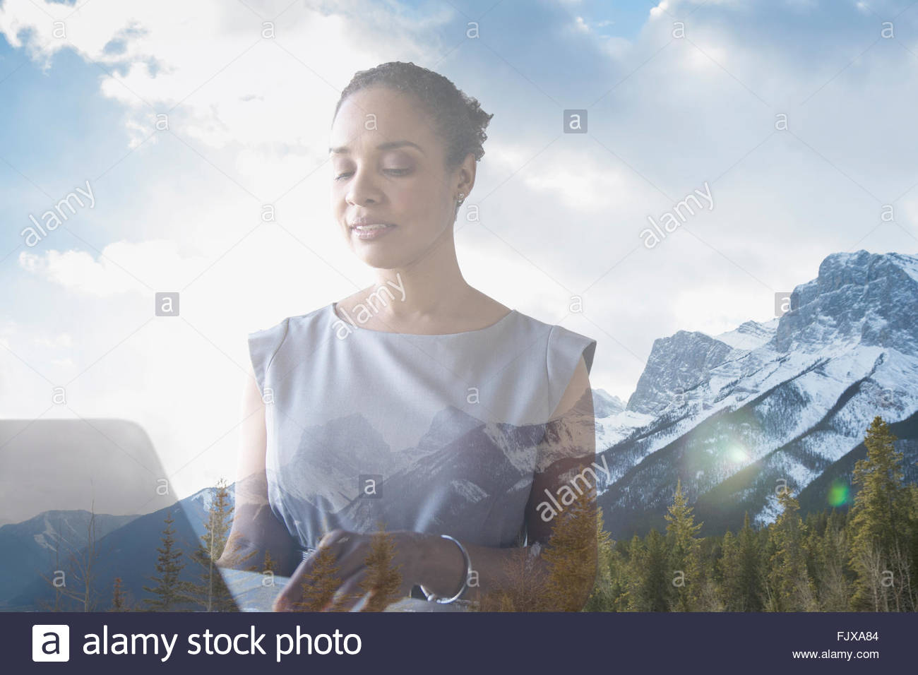 Digital composite businesswoman using laptop against mountains - Stock Image