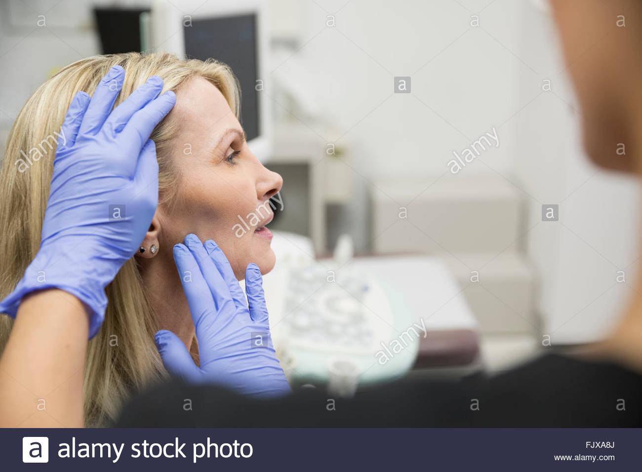 Plastic surgeon with rubber gloves examining womans cheek - Stock Image