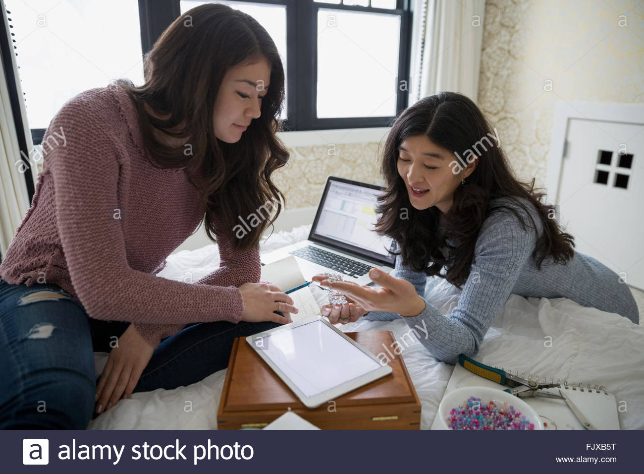 Mother and teenage daughter making jewelry on bed - Stock Image
