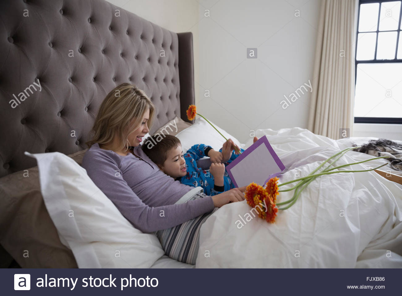 son giving mother mothers day card bed 30-34 - Stock Image