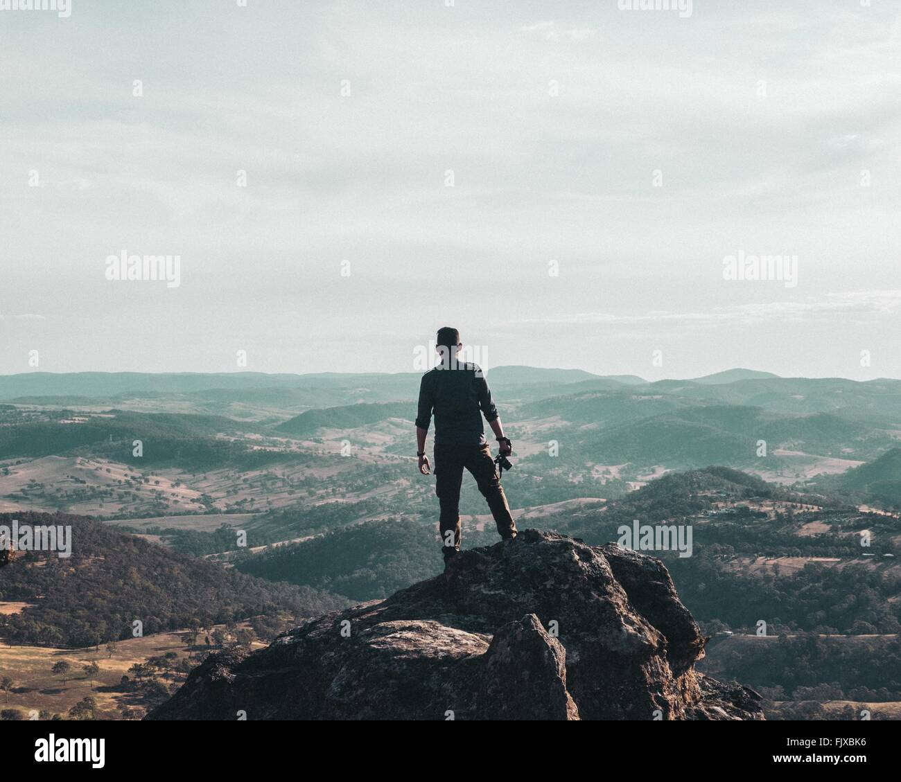 Rear View Of Man Standing On Cliff - Stock Image