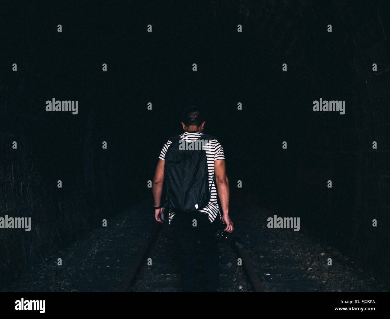 Rear View Of Man Walking On Railroad Track At Night - Stock Image