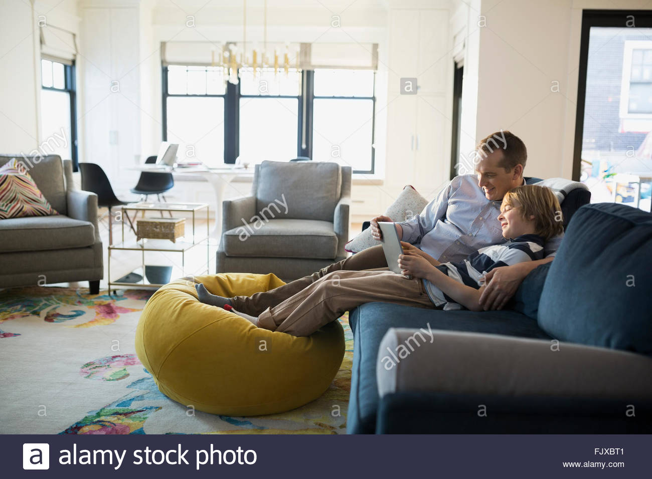Father son sharing digital tablet living room sofa - Stock Image