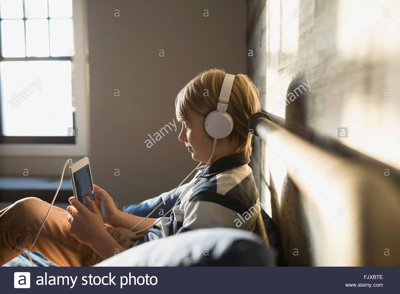 Boy with headphones using digital tablet Stock Photo