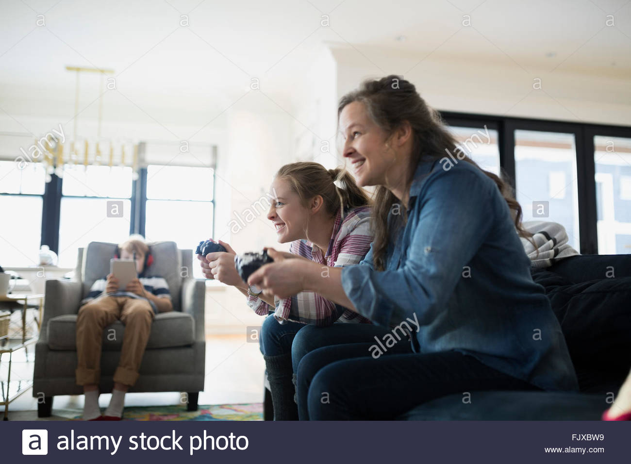 Smiling mother daughter playing video game living room - Stock Image