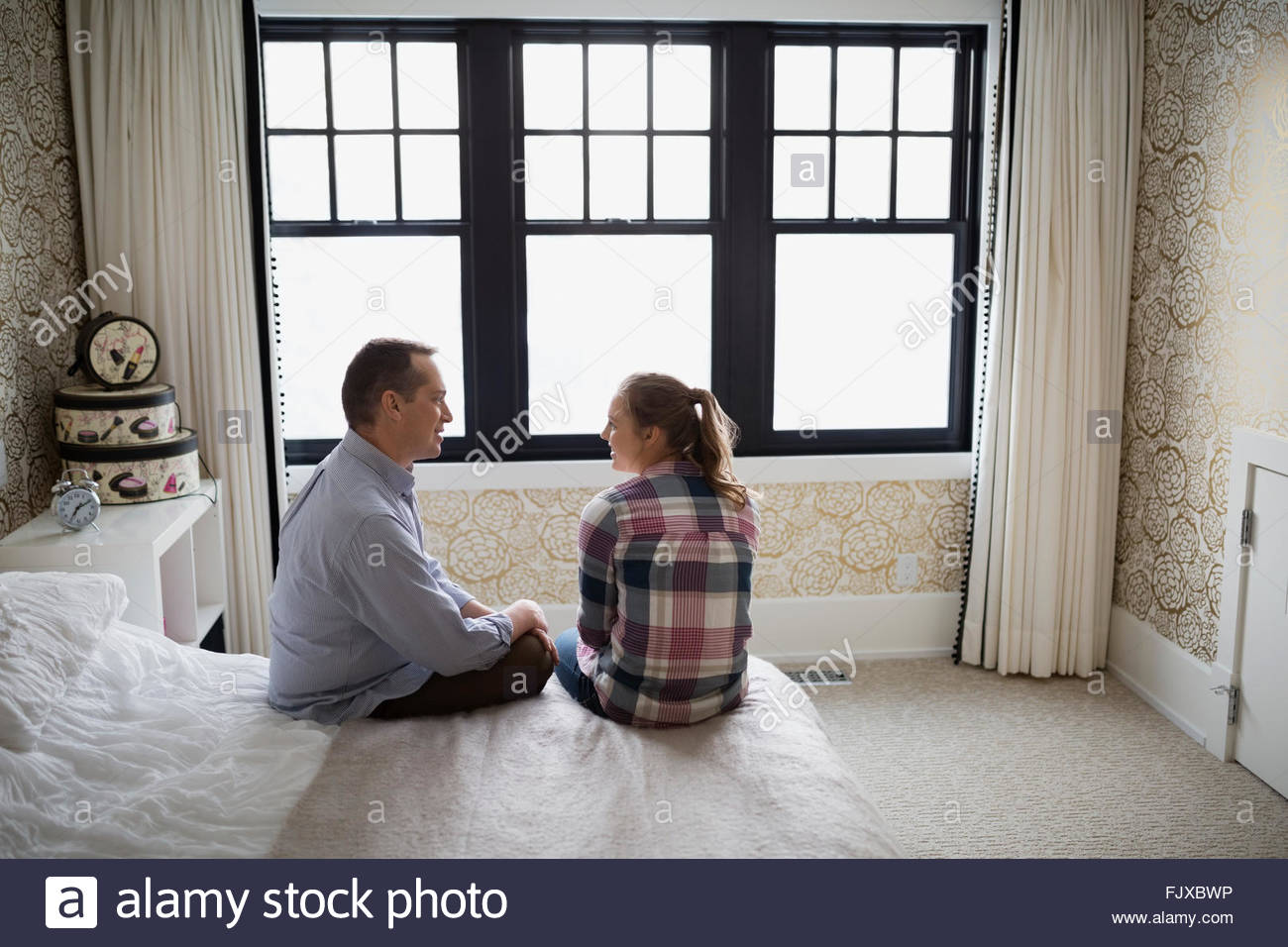 Father and teenage daughter talking in bedroom - Stock Image