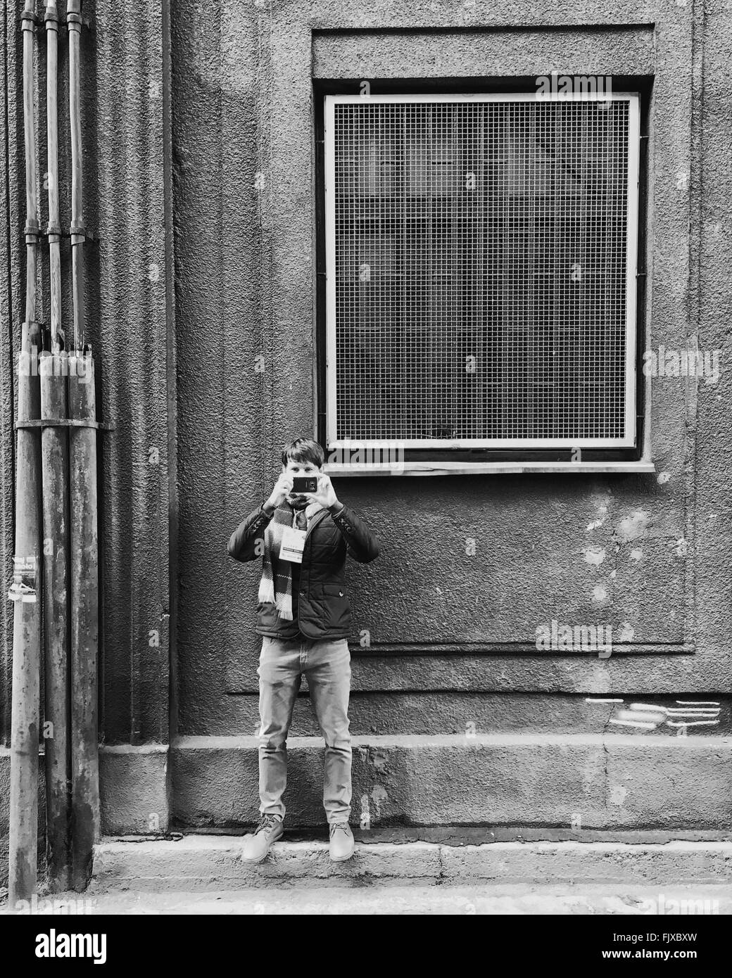 a5b24f9809 Young Man Photographing With Smart Phone While Standing Against Old  Building - Stock Image