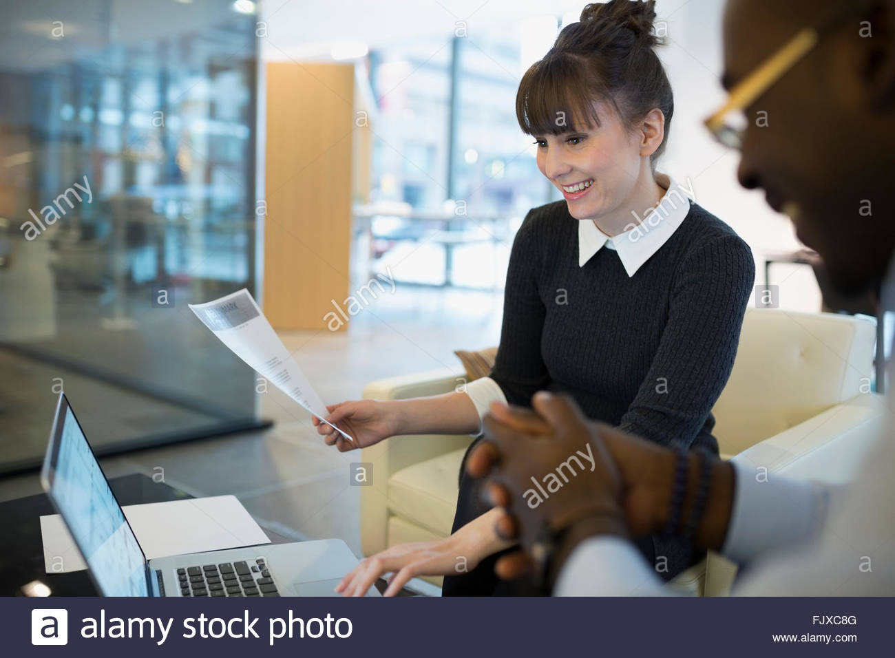 Business people using laptop in office lobby - Stock Image