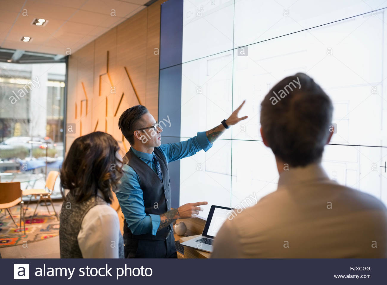 Architects discussing blueprints on projection screen conference room - Stock Image