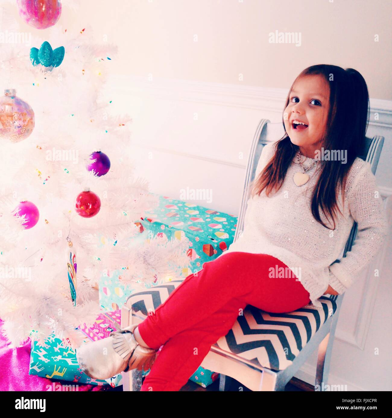 Happy Girl Sitting On Chair By Christmas Tree At Home - Stock Image