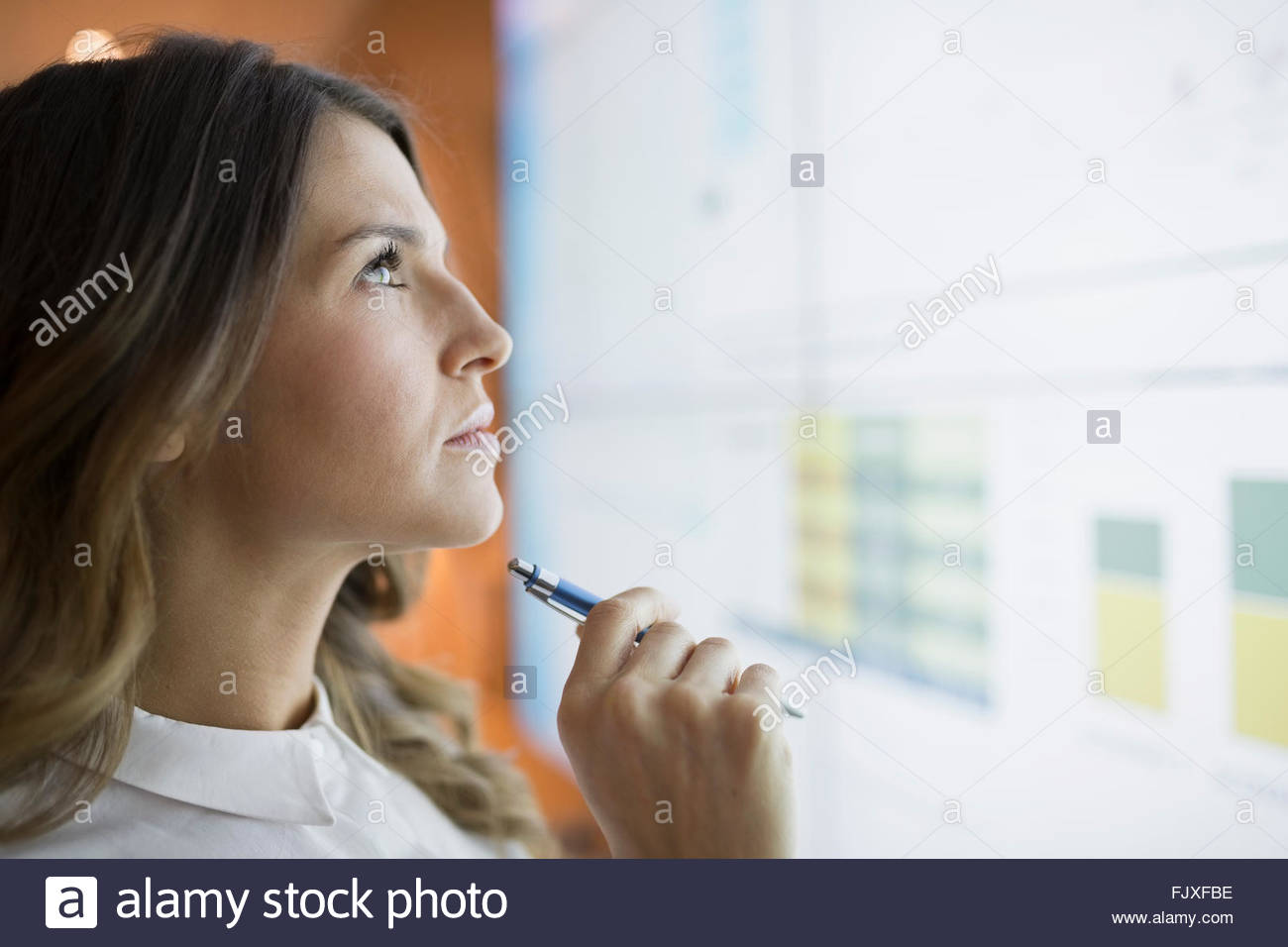 Close up focused businesswoman looking up projection screen - Stock Image