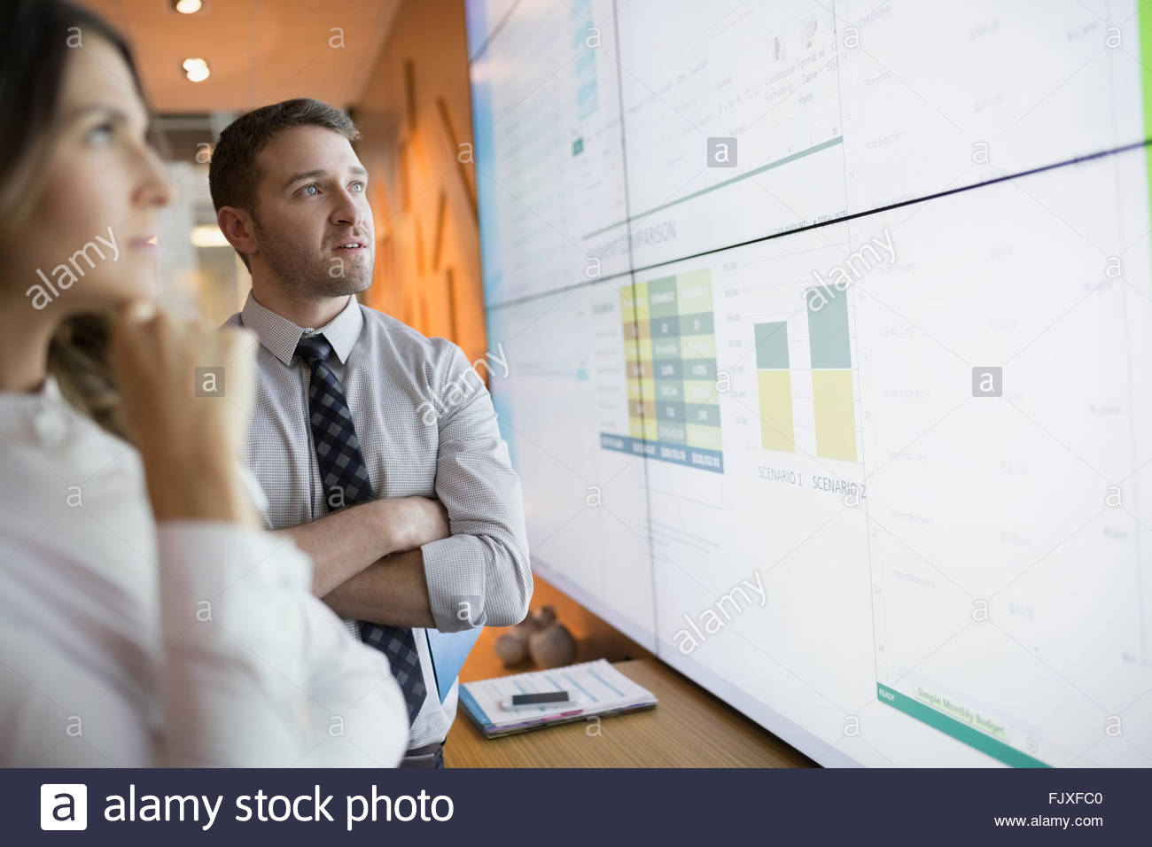 Business people looking up data on projection screen - Stock Image