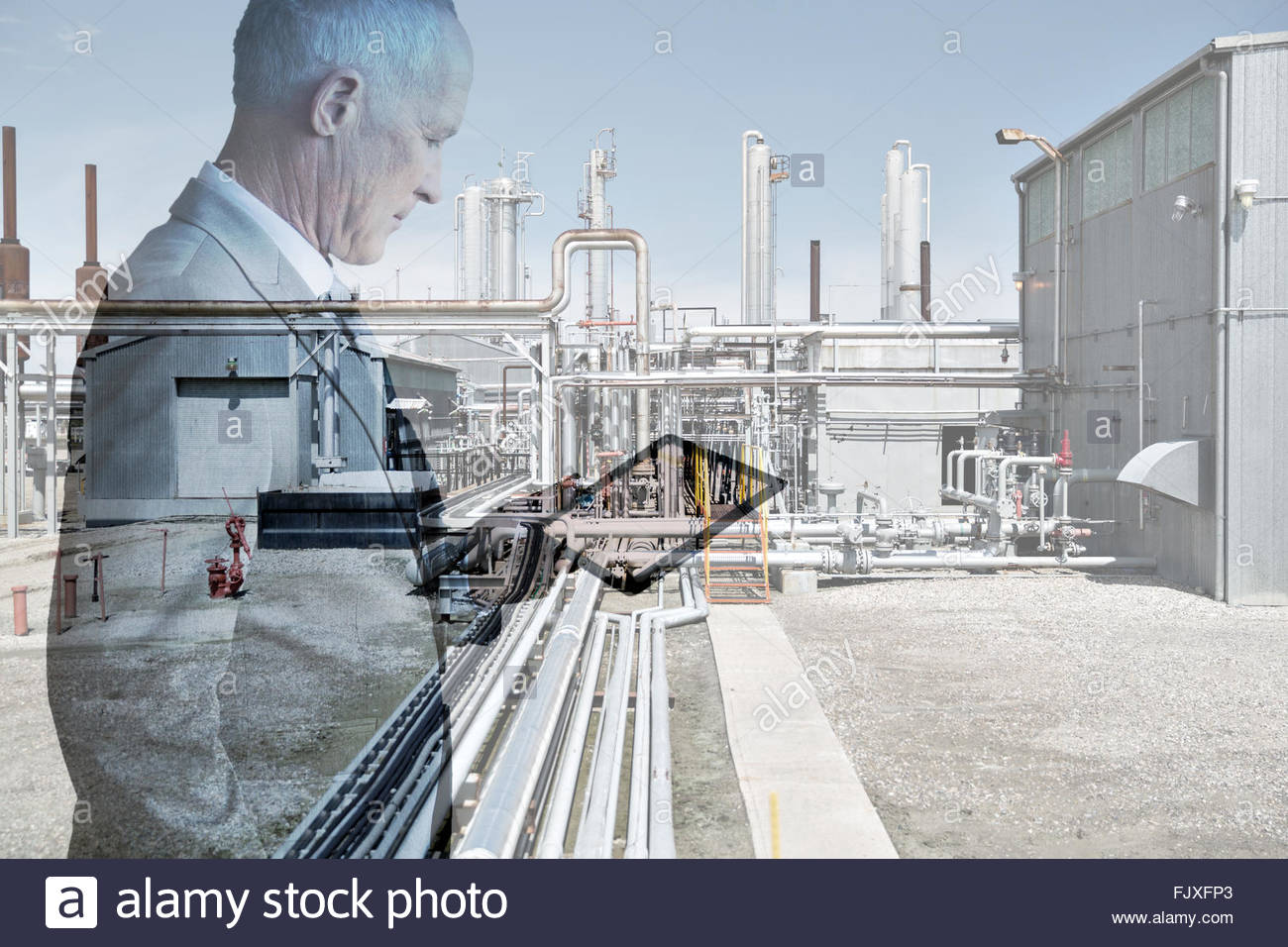 Digital composite businessman using digital tablet at factory - Stock Image