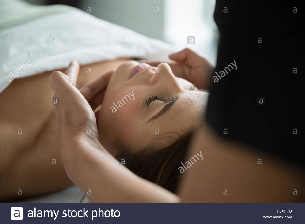 Serene woman with eyes closed receiving spa facial - Stock Image